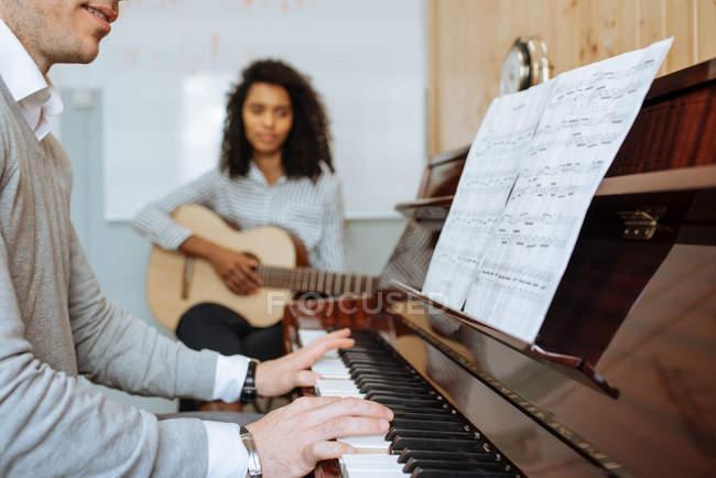 Seitenansicht eines jungen Mannes, der neben einer schwarzen Frau Klavier spielt und im Musikstudio Gitarre spielt — Stockfoto