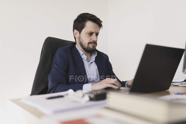 Concentrated young male browsing on laptop at table in office — Stock Photo