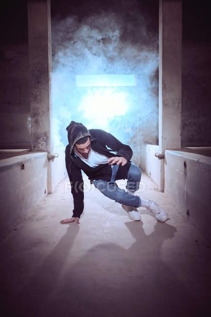 Homem novo no equipamento à moda que executa o movimento do breakdance no fumo ao dançar dentro do edifício gasto — Fotografia de Stock
