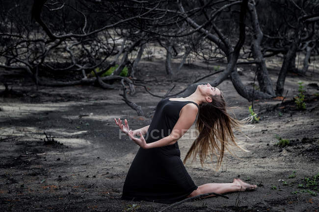 Young ballerina in black wear posing on land between dry woods — Stock Photo