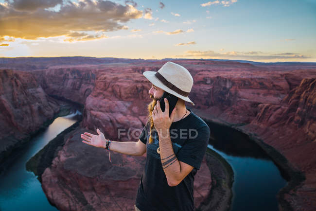 Man in hat speaking on the mobile phone while standing against canyon and river during sunset on West Coast of USA — Stock Photo