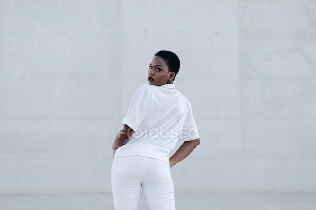 Elegant trendy short haired woman in white outfit posing against grey construction — Stock Photo