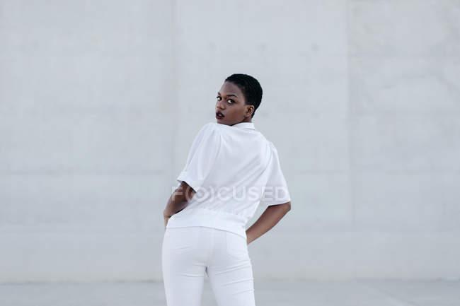 Elégante femme aux cheveux courts tendance en tenue blanche posant contre la construction grise — Photo de stock