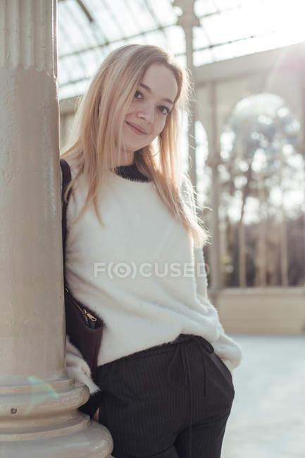 Стильная улыбающаяся молодая женщина, опираясь на пост в Кристал Пэлас в Мадриде, Испания — стоковое фото
