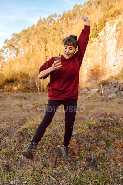 Young hipster woman with upped hand listening music on mobile phone and dancing in nature — Stock Photo