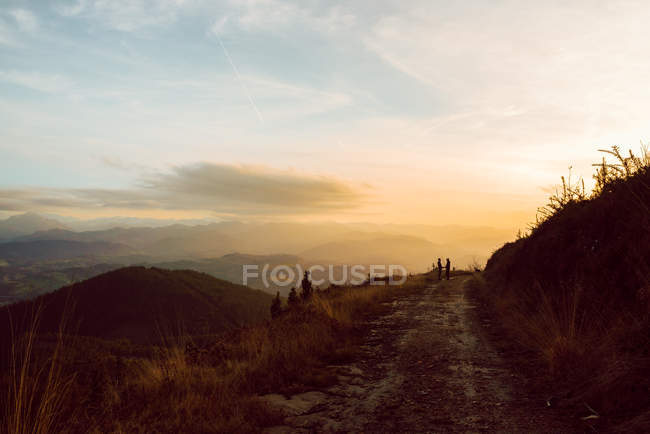 Distant homosexual couple embracing near dog on route in mountains at sunset — Stock Photo