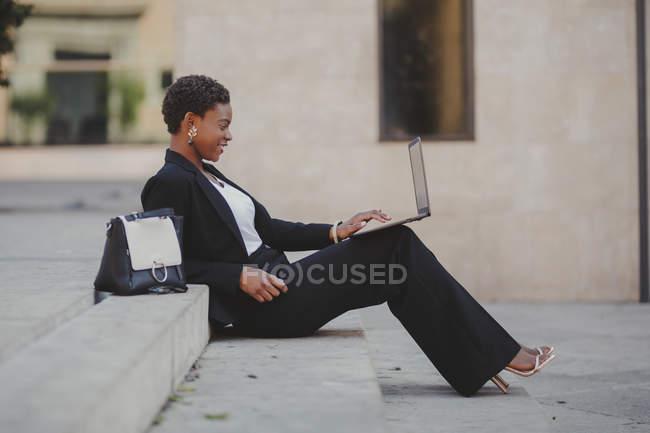 Encantadora mujer elegante afroamericana confiada en traje de navegación en el ordenador portátil y sentado en las escaleras cerca de la bolsa en la calle - foto de stock