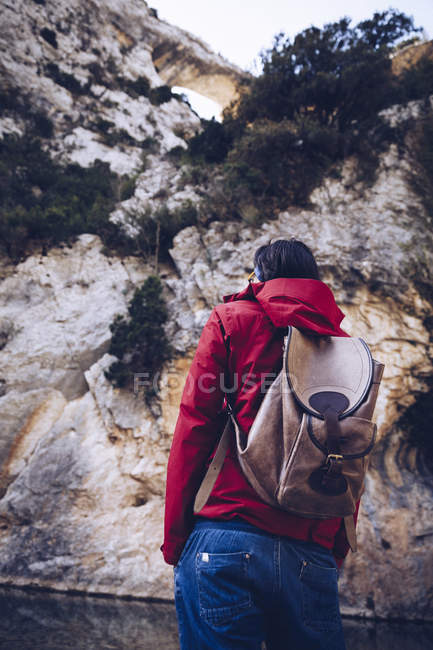 Back view of male with backpack on coast of mountain river near rock mountain — Stock Photo