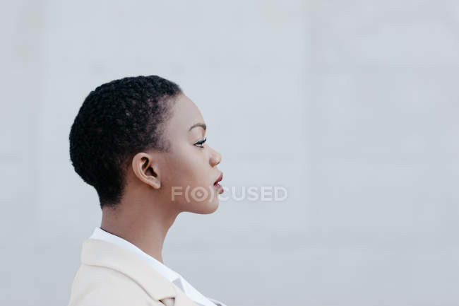 Close-up of short haired ethnic woman posing against grey wall — Stock Photo