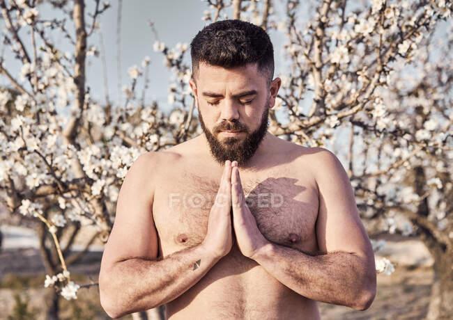 Homme torse nu méditant dans le jardin de printemps — Photo de stock