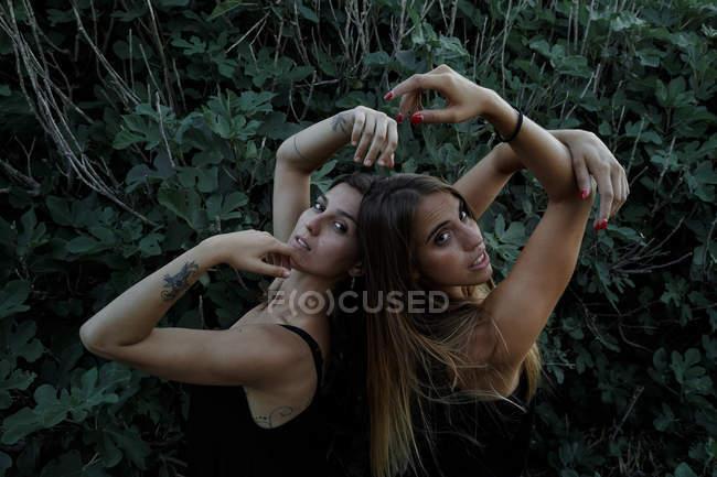 Вид сбоку на привлекательных молодых женщин с закрытыми глазами и поднятыми руками, стоящих возле зеленого кустарника — стоковое фото