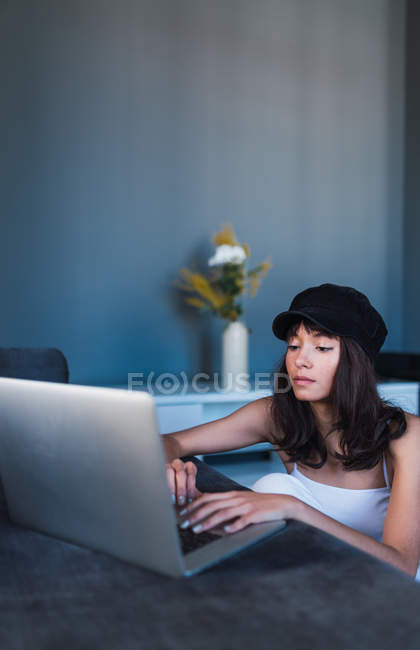 Attractive young stylish woman in cap using laptop at home — Stock Photo