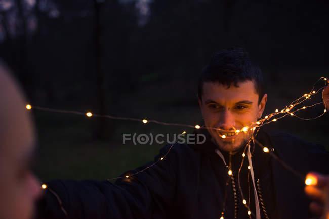 Крупный план мужчин, распутывающих светящиеся волшебные огни в темном лесу вечером на размытом фоне — стоковое фото