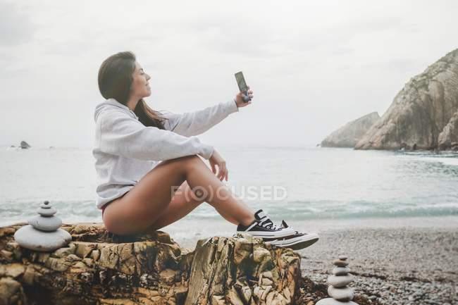 Весела жінка в пуловер і взуття приймаючи селфі з мобільним телефоном на узбережжі — стокове фото