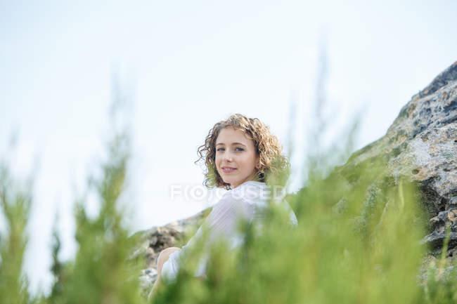 Молода чарівна жінка сидить між скелею і гілок і дивиться на камеру — стокове фото