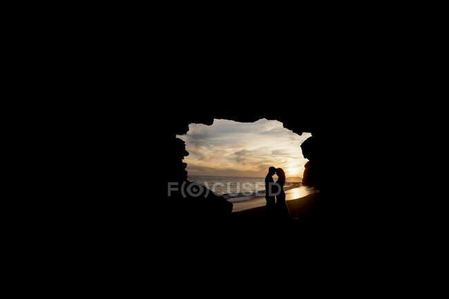 Vista lateral de los recién casados abrazándose en la cueva oscura en la costa de arena cerca del agua y el cielo azul al atardecer - foto de stock