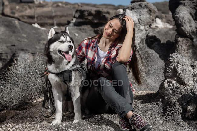 Joyeuse jeune femme assise près husky sur le rocher — Photo de stock