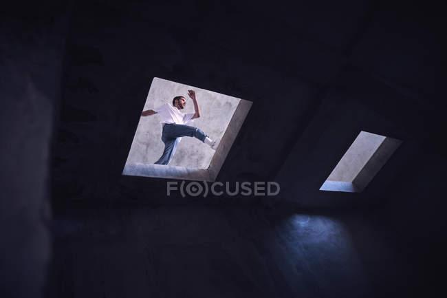 De baixo jovem em roupa casual pulando sobre buraco no telhado do edifício grungy enquanto dança dança dança moderna na rua — Fotografia de Stock