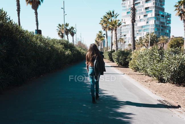Adolescente marchant joyeusement dans les rues de la ville par une journée ensoleillée — Photo de stock