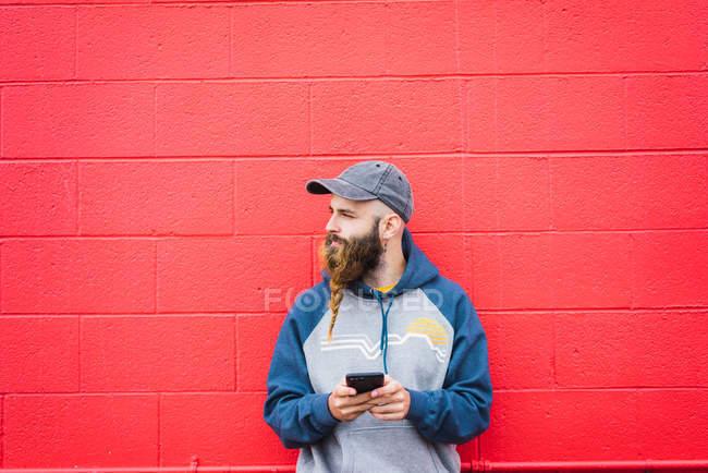 Attraente ragazzo con la barba intrecciata smartphone di navigazione mentre si appoggia muro rosso sulla strada della città — Foto stock