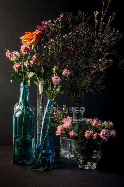 Glasvasen mit Blumensträußen auf schwarzem Hintergrund — Stockfoto