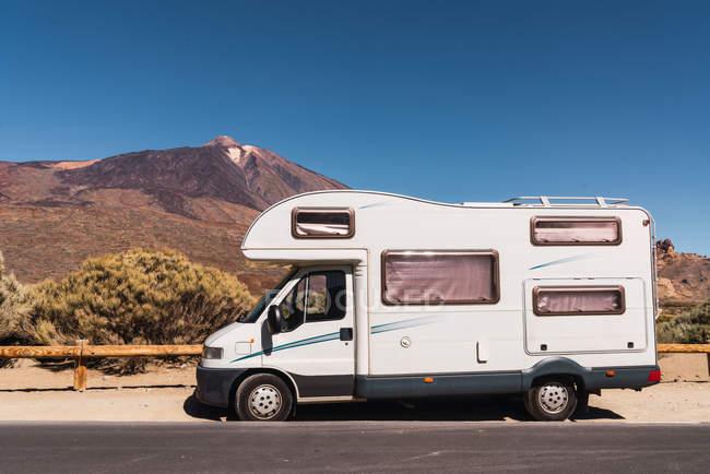 Кемпер Ван припаркований на асфальті дороги біля мальовничого погляду на сині небеса і гірські Тейде на Тенеріфе, Канарські острови, Іспанія — стокове фото
