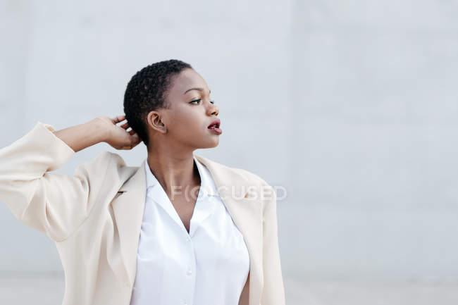 Elegante donna etnica dai capelli corti alla moda in posa contro il muro grigio — Foto stock