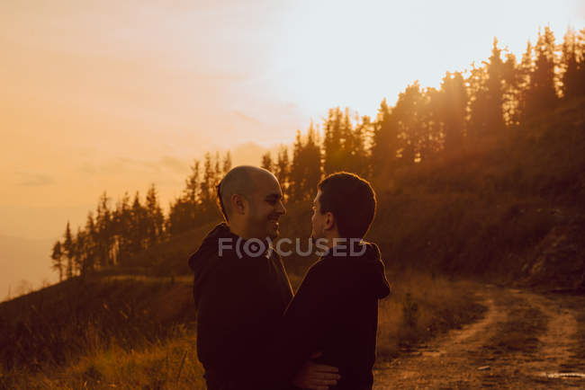 Happy homosexual couple hugging on path in forest in sunny day — Stock Photo