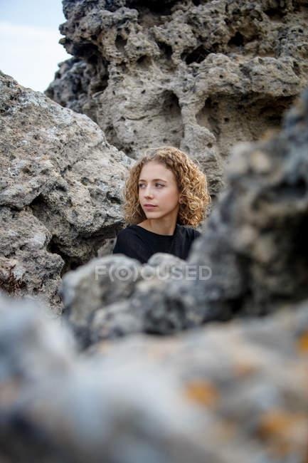 Junge nachdenkliche Frau sitzt in Steinen und schaut weg — Stockfoto