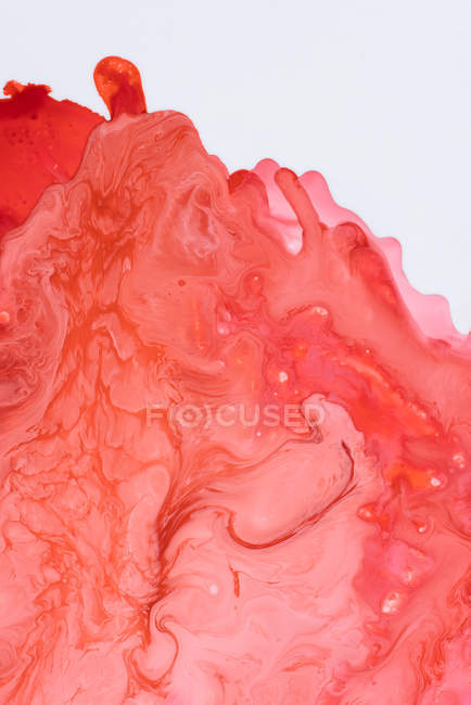 Abstraction of liquid paints in slow blending flow mixing together gently on white background — Stock Photo