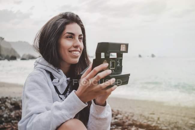 Усміхнена молода жінка тримає камеру на пляжі — стокове фото