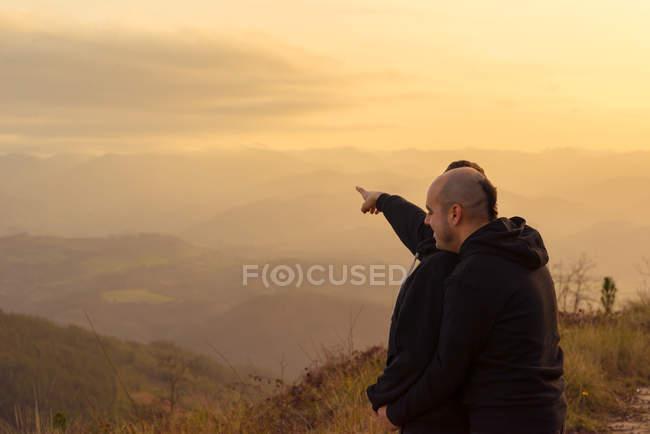 Coppia omosessuale in piedi sulla strada in montagna e guardando la vista — Foto stock