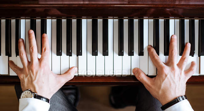 Crop top view of man hands playing piano in a music studio — Stock Photo