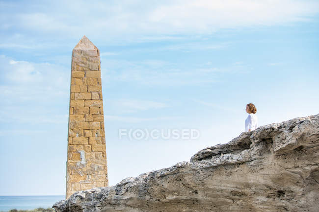 Pensive woman standing near stone construction in form of tower on rocky sea coast — Stock Photo