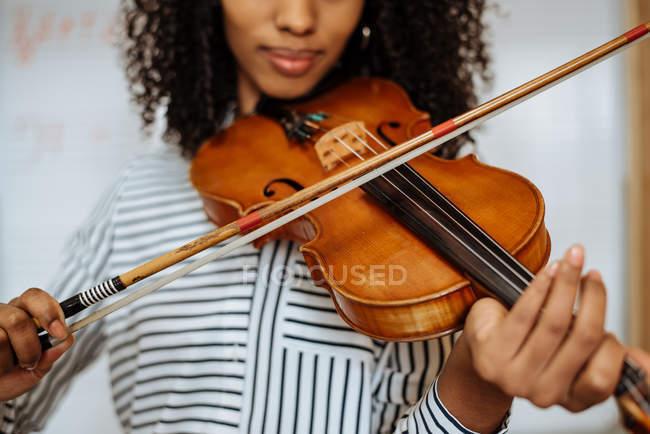 Junge Frau spielt Geige mit Schreibtafel im Hintergrund im Musikstudio — Stockfoto