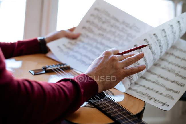 Erntehelfer mit Notenblättern beim Gitarrespielen während der Probe im Studio. — Stockfoto