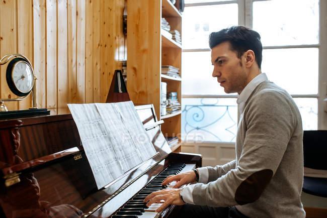 Schöner Mann beim Klavierspielen während der Probe im Tonstudio. — Stockfoto