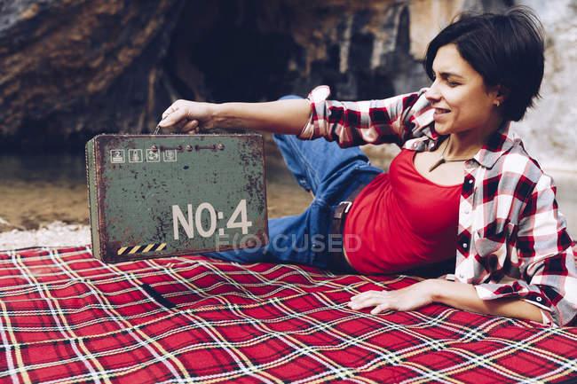 Sorrindo mulher adulta deitada em xadrez na margem do lago em falésias segurando velho caso enferrujado com provisão sorrindo para a câmera — Fotografia de Stock