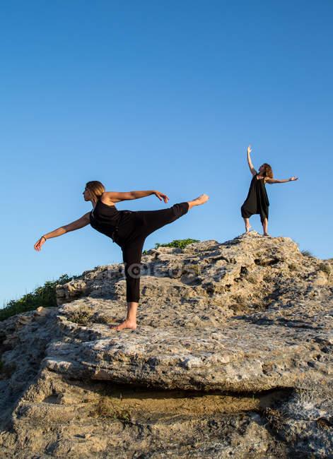 Junge geheimnisvolle Ballerinen in Schwarz tanzen an sonnigen Tagen auf Felsen — Stockfoto