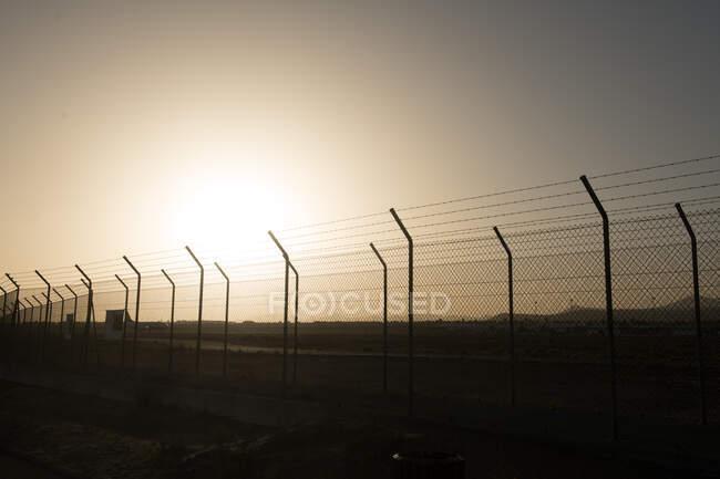 Sol brilhante atrás da cerca de segurança — Fotografia de Stock