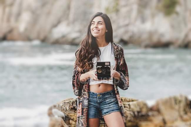 Усміхнена молода жінка тримає камеру на морському узбережжі — стокове фото