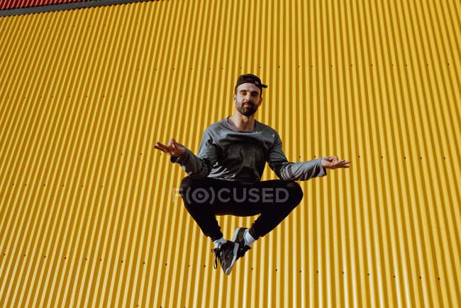 Cara barbudo na roupa da moda pulando e olhando para a câmera contra a parede amarela do edifício moderno no dia ensolarado — Fotografia de Stock