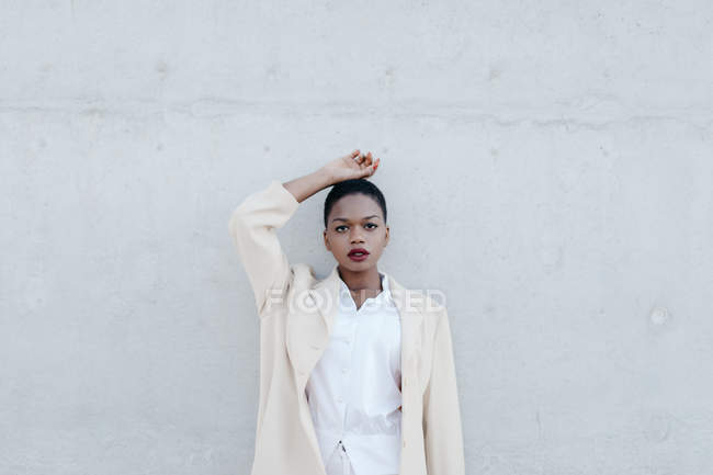 Elégante femme ethnique aux cheveux courts tendance en tenue blanche posant contre un mur gris — Photo de stock