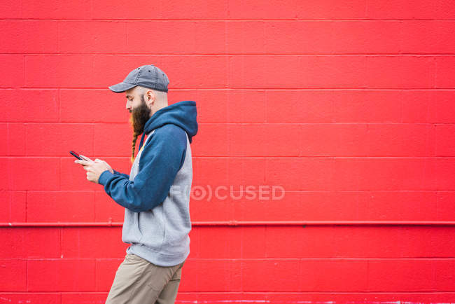 Side view of attractive guy with braided beard browsing smartphone while walking near red wall on city street — Stock Photo