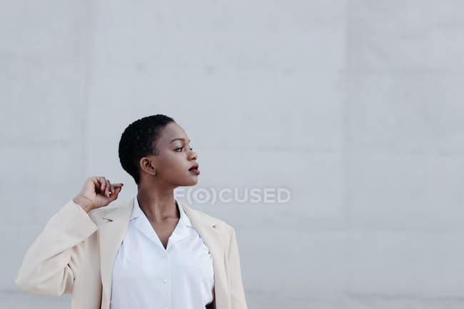 Елегантний модний короткий волосся етнічної жінки в білому Екіпіровка видаючи себе за сірої стіни — стокове фото