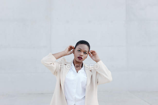Elegant trendy short haired ethnic woman in white outfit posing against grey wall — Stock Photo