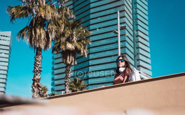 Teenie-Mädchen beobachtet die Straße, während sie mit Helm und Smartphone Musik hört — Stockfoto