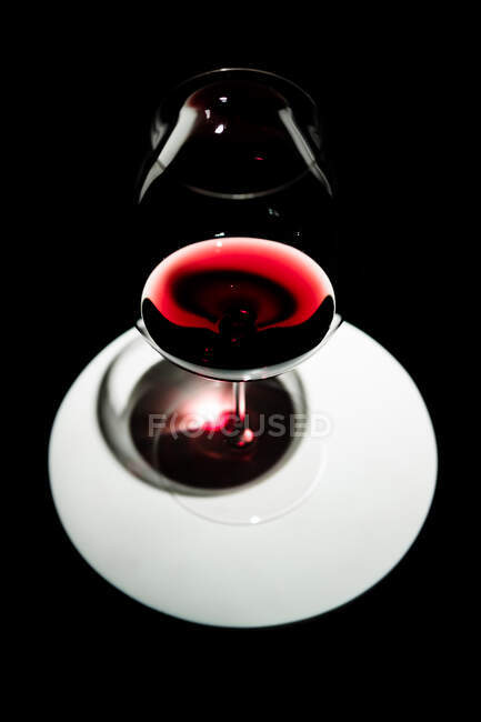 From above glass of red wine on white dish on black background — Stock Photo