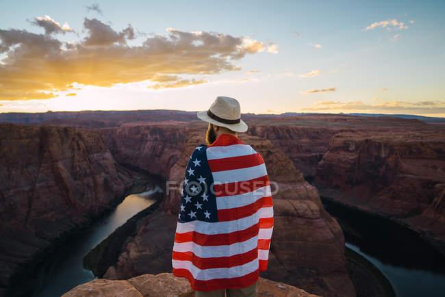 Rückansicht eines Mannes, der mit einer US-Flagge umhüllt in der Nähe einer schönen Schlucht gegen den Abendhimmel an der Westküste steht — Stockfoto