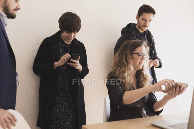 Giovani uomini e donne che conversano, navigano sul cellulare e digitano sul computer portatile al tavolo in ufficio — Foto stock